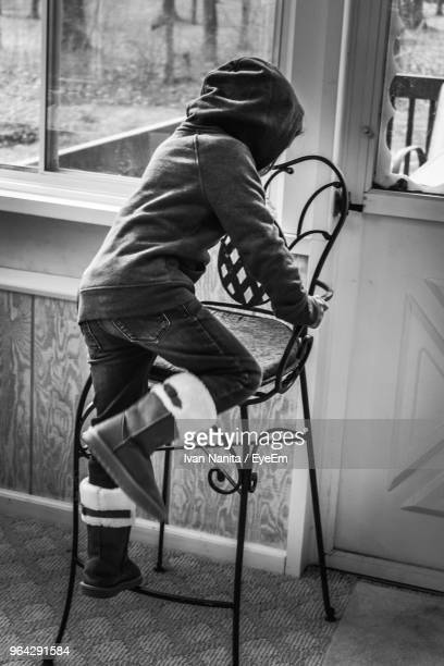 Rear View Full Length Of Child On Chair At Home