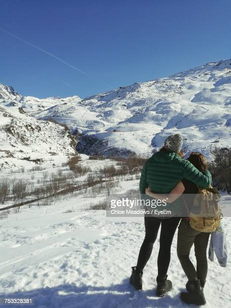 rear view full length of couple on snow covered field at les menuires - trois vallees - fotografias e filmes do acervo