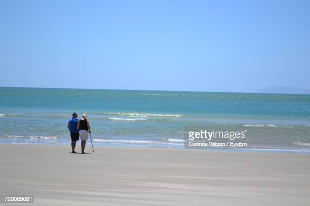rear view full length of couple standing on shore at beach against clear sky - corinne paradis photos et images de collection