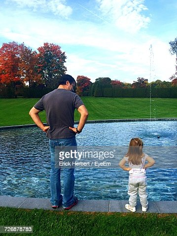 Rear View Full Length Of Father Standing With Daughter By Fountain At Park During Autumn