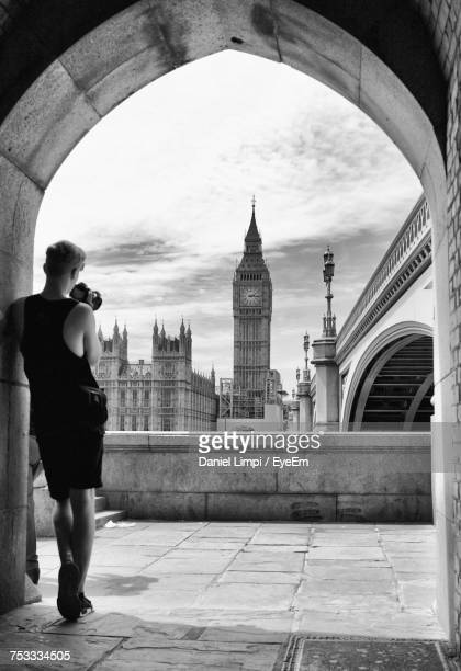 rear view full length of man photographing big ben while standing at archway in city - history stock-fotos und bilder