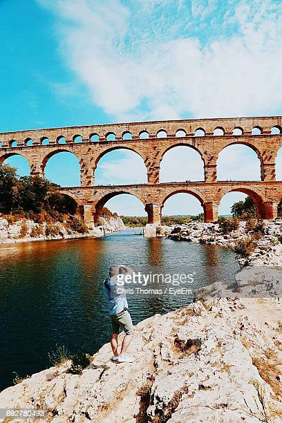 Rear View Full Length Of Man Photographing Pont Du Gard By River Gardon