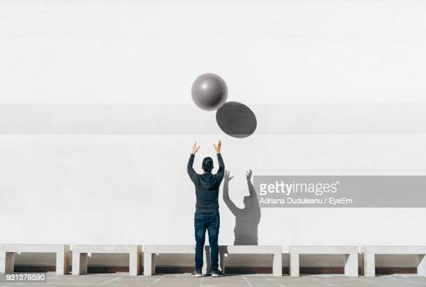 Rear View Full Length Of Man Playing With Ball Against Wall
