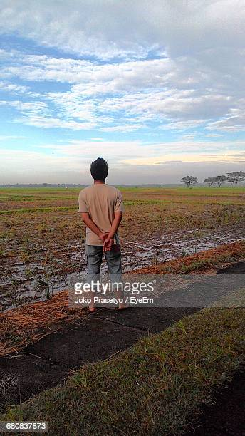 Rear View Full Length Of Man Standing Against Agricultural Landscape