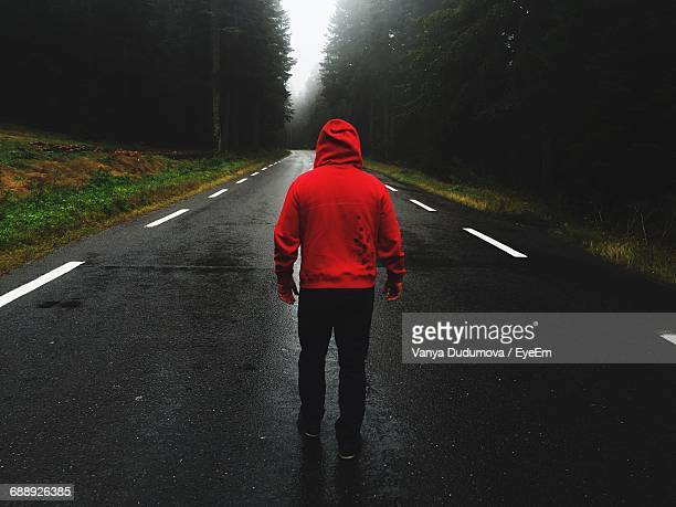 Rear View Full Length Of Man Standing On Road Amidst Trees