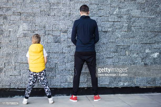 rear view full length of man urinating with son against stone wall - kids peeing stock pictures, royalty-free photos & images