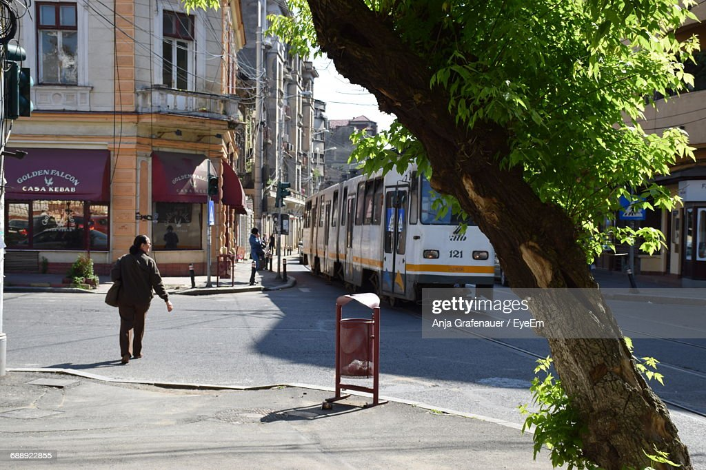 Rear View Full Length Of Man Walking By Cable Car On Street In City : Stock Photo