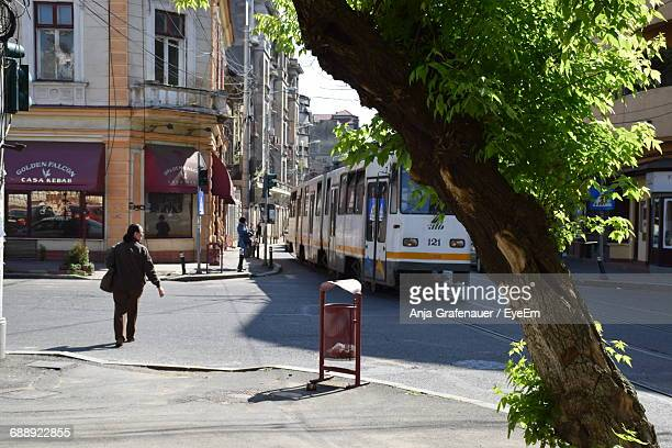 rear view full length of man walking by cable car on street in city - bucharest stock pictures, royalty-free photos & images