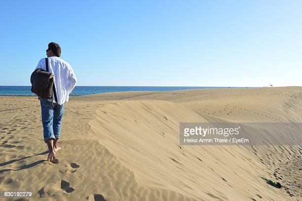 Rear View Full Length Of Man Walking On Sand Against Clear Sky