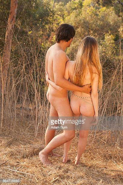 rear view full length of naked couple standing in nature - bare bottom women stock photos and pictures
