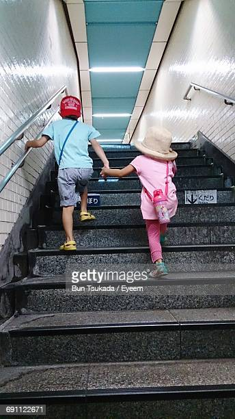 Rear View Full Length Of Siblings Moving Up On Steps In Station