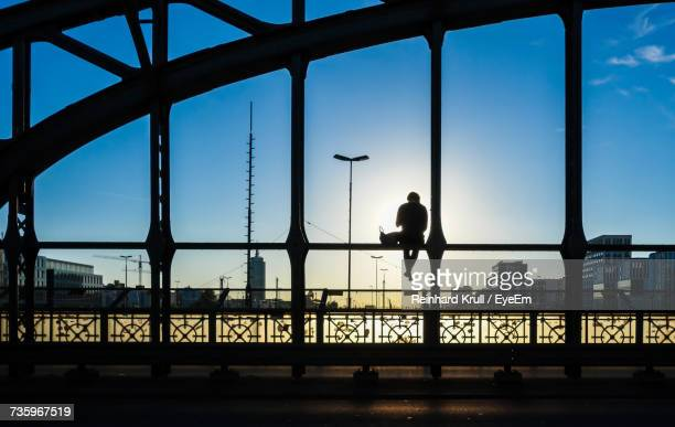 Rear View Full Length Of Silhouette Person Sitting At Hackerbrucke Bridge Railing