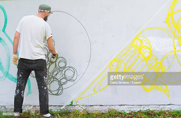 rear view full length of street artist painting graffiti on wall - street artist stock photos and pictures