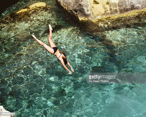 Rear View Full Length Of Woman Diving Into Sea