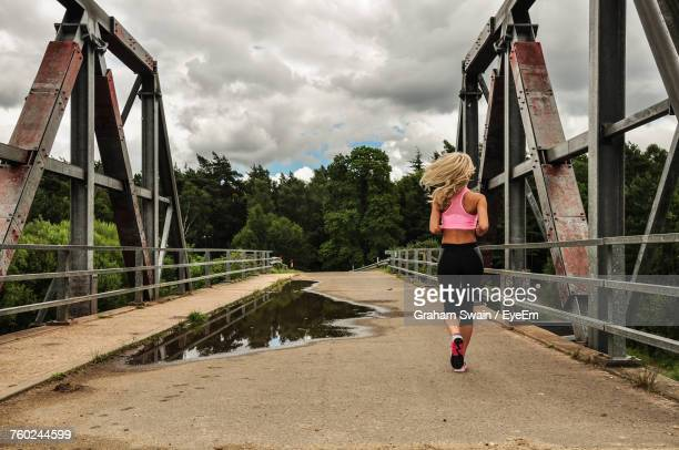 Rear View Full Length Of Woman Jogging On Bridge Against Cloudy Sky