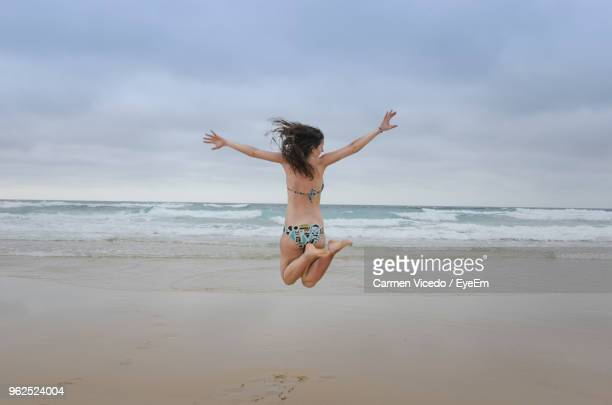 Rear View Full Length Of Woman Jumping At Beach Against Sky