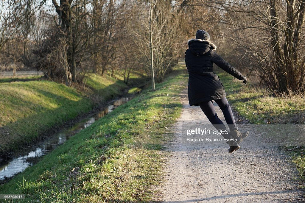 Rear View Full Length Of Woman Jumping On Walkway : Stock Photo