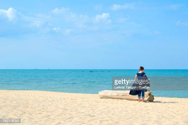 Rear View Full Length Of Woman Removing Jacket At Beach Against Sky