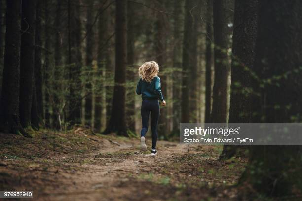 rear view full length of woman running at forest - bos stockfoto's en -beelden