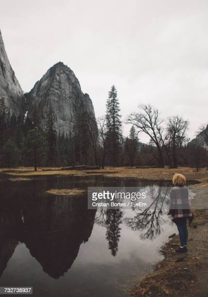 rear view full length of woman standing by calm lake at yosemite national park - bortes stock photos and pictures