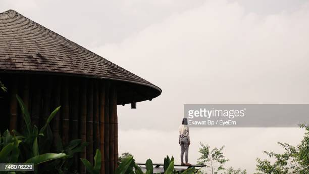 Rear View Full Length Of Woman Standing By Hut Against Sky