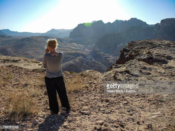 Rear View Full Length Of Woman Standing On Mountain On Sunny Day