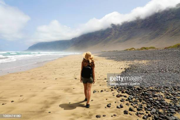 rear view full length of woman walking at beach - lanzarote stock pictures, royalty-free photos & images