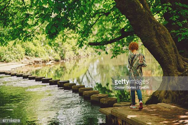 Rear View Full Length Of Woman Walking On Stepping Stones By Pond At Park