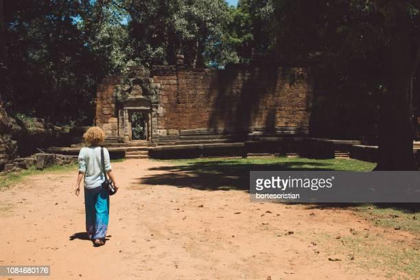 rear view full length of woman walking towards temple - bortes foto e immagini stock