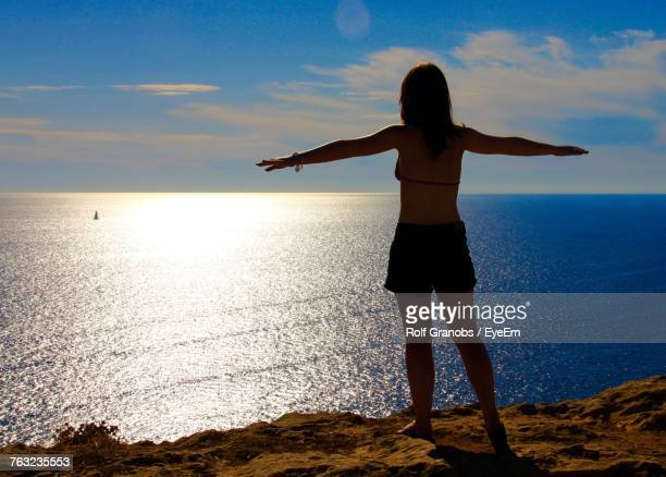 Rear View Full Length Of Woman With Arms Outstretched On Cliff Against Sea During Sunny Day