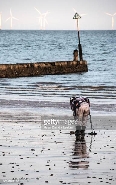 Rear View Full Length Of Woman With Metal Detector At Beach