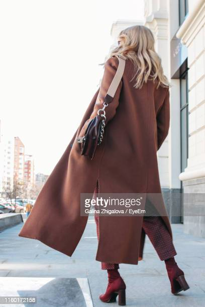 rear view full length of young woman wearing long coat standing on sidewalk in city - long coat stock pictures, royalty-free photos & images