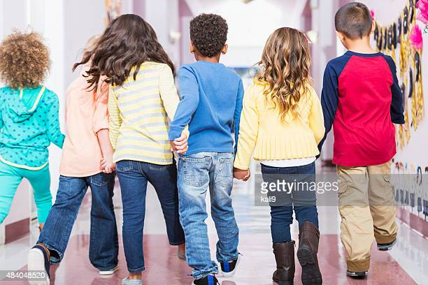 rear view, group of preschoolers walking down hallway - unrecognisable person stock pictures, royalty-free photos & images