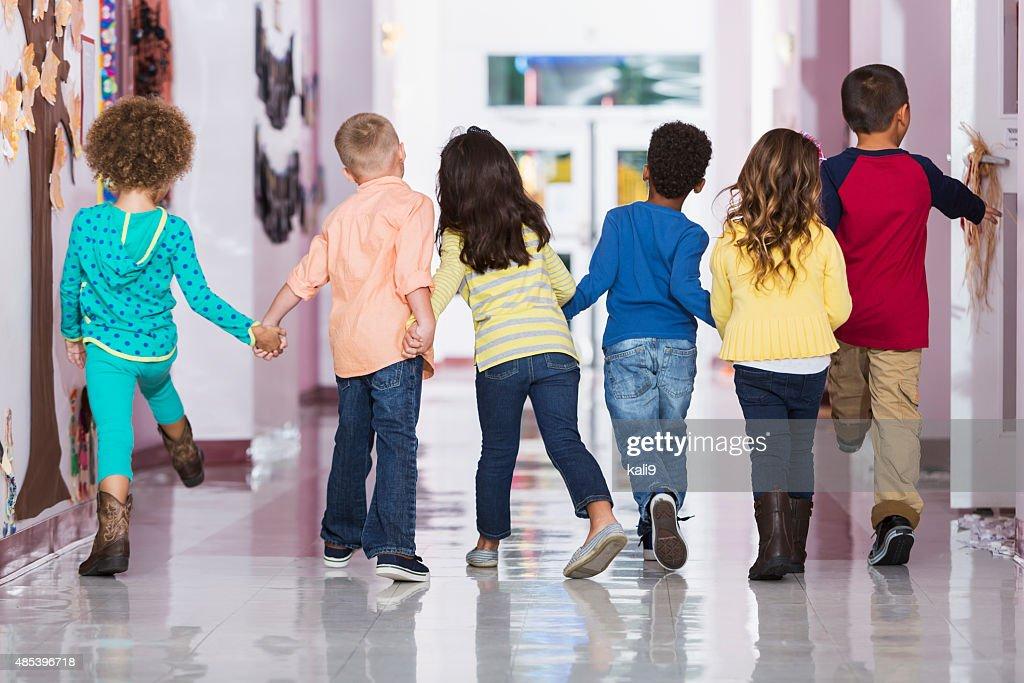 Vue de dos, groupe de preschoolers marchant le long couloir : Photo