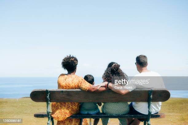 rear view happy mixed race family sitting  at bench in a public park having fun - bench stock pictures, royalty-free photos & images