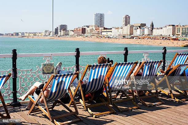 rear view holiday makers in deckchairs at brighton - brighton beach england stock pictures, royalty-free photos & images
