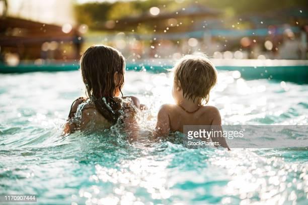 petite vue arrière petit garçon et fille s'asseyant et éclaboussures dans la piscine - piscine photos et images de collection