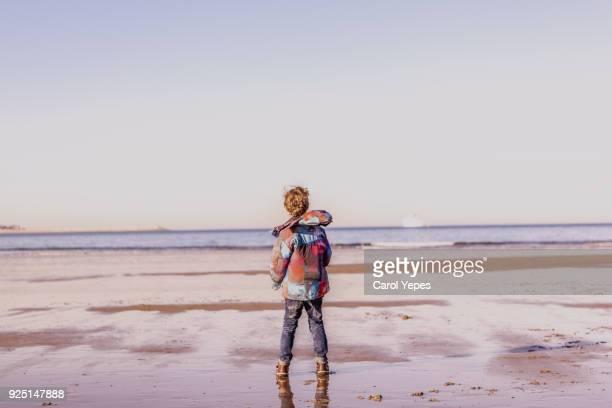 rear view little boy in raincoat at the beach - tidvattensbassäng bildbanksfoton och bilder