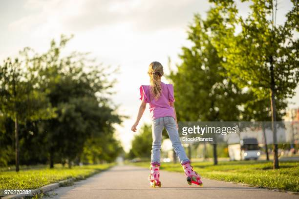 rear view little girl on roller skates - petite teen girl stock photos and pictures