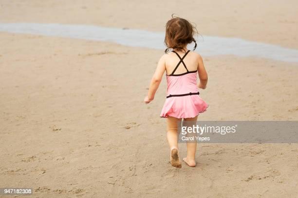 rear view little girl walking in the sand