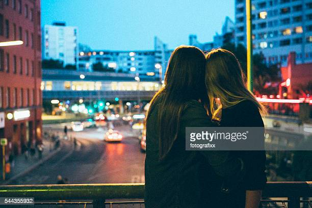 rear view, loving women couple looking looking at city lights - kreuzberg stock photos and pictures