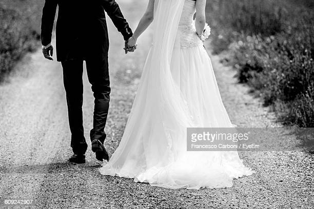 rear view low section of wedding couple walking on gravel road - marriage stock pictures, royalty-free photos & images