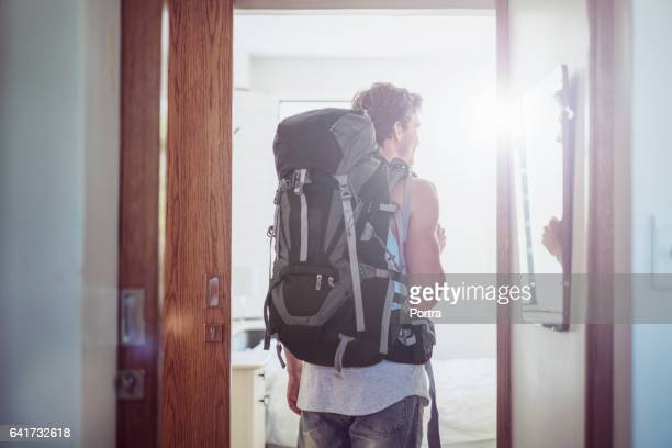 Rear view male tourist entering in hotel room
