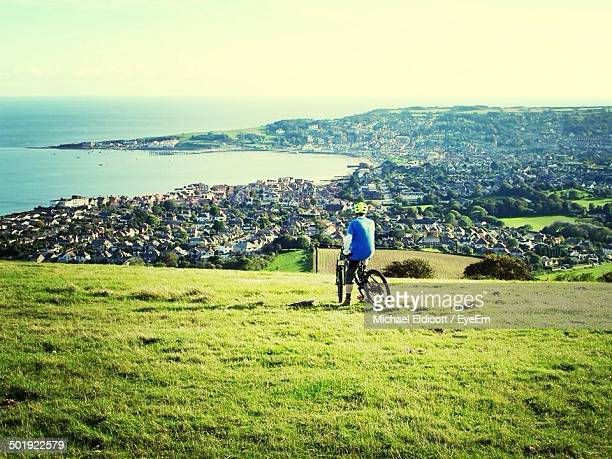 Rear view man on mountain bike overlooking cityscape