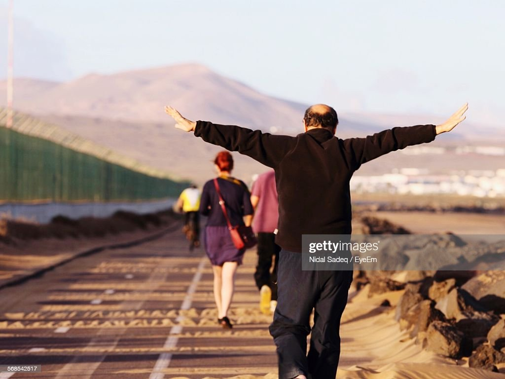 Rear View Man Walking With Arms Outstretched On Road : Stock Photo