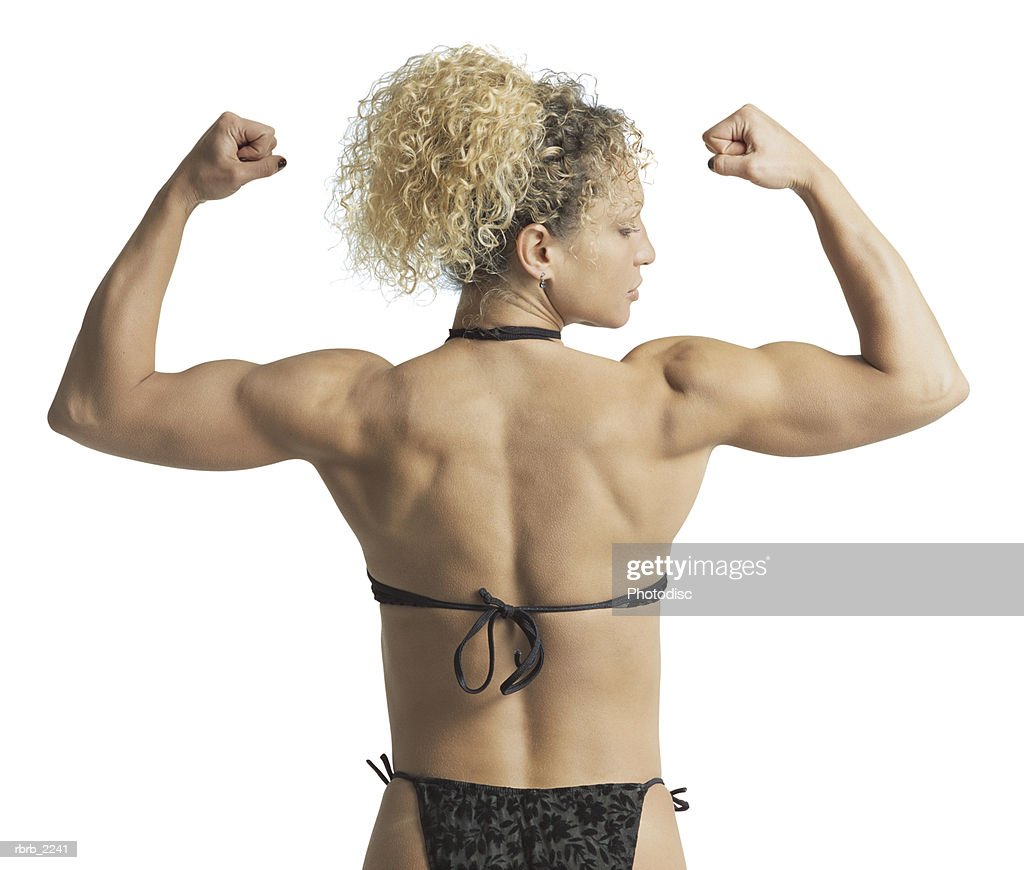 rear view medium shot of an adult female body builder as she flexes her muscles : Foto de stock