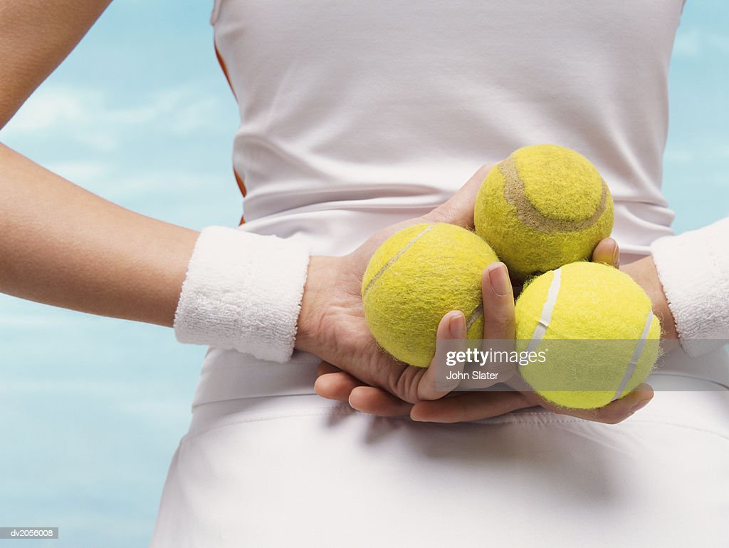 Rear View Mid Shot of a Female Tennis Player Holding Three Tennis Balls Behind Her Back : Stock Photo