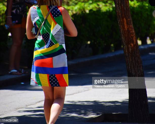 Rear View Midsection Of Woman Wearing Colorful Dress While Walking On Street