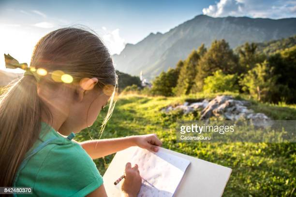 Rear View Of 8 Years Old Girl Drawing The View Of The Mountain Range