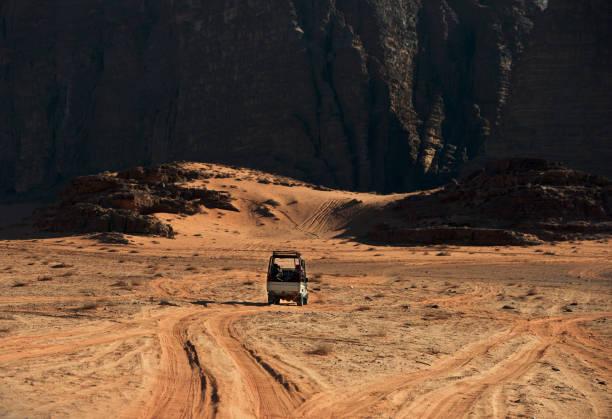 Rear view of a 4x4 driving through the desert, Wadi Rum, Jordan